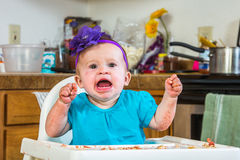 Baby Has a Tantrum. A baby girl throws a tantrum in the kitchen royalty free stock photo