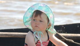 Baby in hat. Portrait of beautiful baby in blue  hat on the retro boat Royalty Free Stock Images