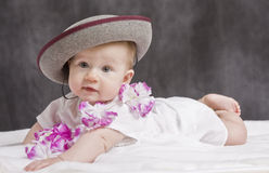 Baby with hat. And white dress lying Royalty Free Stock Images