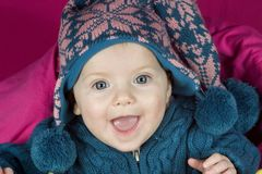 Baby in hat. A blue eyed baby in a winter hat smiling Royalty Free Stock Images