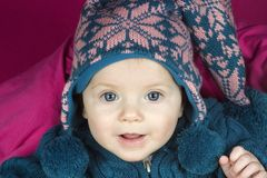 Baby in hat. A blue eyed baby in a winter hat smiling Royalty Free Stock Photo