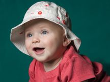 Baby in Hat. Baby in fish print hat smiling on green background Stock Images