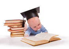 Baby in a hat of the bachelor and the book Royalty Free Stock Images