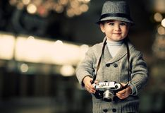 Baby in hat with camera. Baby boy with retro camera over blurred background Royalty Free Stock Photos