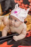 Baby in hat crawling on bed. Baby without clothes in a hat with a picture crawling on black bedding Stock Image