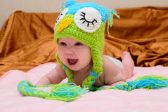 Baby in a hat crawling on the bed Royalty Free Stock Photo