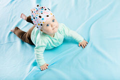 Baby in hat crawling on the blue coverlet Stock Photography