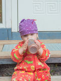 The baby in the hat eats from the bottle. royalty free stock photos