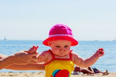 Child holding adult hands on beach stock images