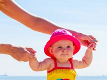 Child holding adult hands on beach Stock Photography
