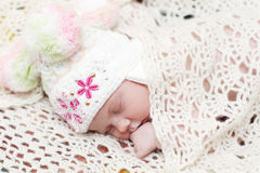 Baby in hat lies on bed under white knitted shawl Royalty Free Stock Photography