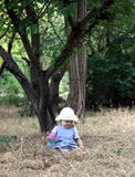 The baby in a hat. The little girl sits in a grass under a tree and smiles. Vertical photo Stock Image