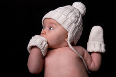 Baby in Hat and Mittens on Black Stock Photo