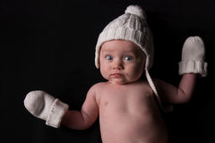 Baby in Hat and Mittens on Black Royalty Free Stock Photography