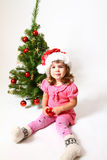 Baby with hat of Santa Claus and Christmas tree Stock Photos