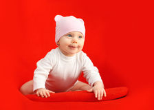 Baby in hat sitting and playing on the red armchair Royalty Free Stock Photos