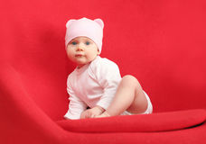 Baby in hat sitting on the red armchair Stock Images