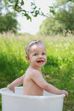 Baby having a bath in the garden. Summer time Royalty Free Stock Photography