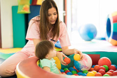 Baby having fun in ball pool. Attractive female therapist playing with a baby in a ball pool in a children therapy center stock image