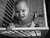 Baby having fun in crib. View on a happy smiling baby boy having fun in crib holding on sides Stock Image