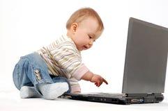 Baby having fun with laptop Stock Image