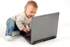 Baby having fun with laptop Stock Images