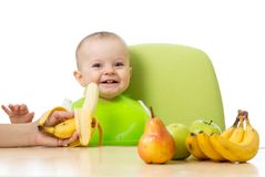 Baby having a table full of healthy food. Cheerful toddler with fruits apples, bananas, pear. Isolated on white Royalty Free Stock Photography