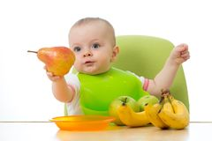 Baby having a table full of healthy fruits. Cheerful toddler holding pear. on white royalty free stock photos