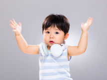 Baby with headphone and hand up Stock Image