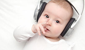 Baby with headphone lies on back. Baby boy with headphone lies on back Royalty Free Stock Image