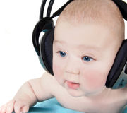 Baby with headphones. Baby listening to music trough the headphones, isolated Stock Image