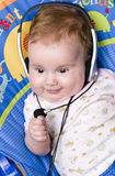 Baby with headphones. Portrait of a funny baby girl wearing headphones and smiling Royalty Free Stock Photos