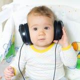 Baby with headphones. Cute baby with headphones looking at camera Royalty Free Stock Image