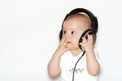 Baby with headphones. Small boy with headphones on wall background stock photos