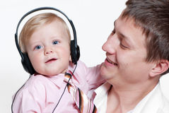 Baby with headphones and father Royalty Free Stock Photography