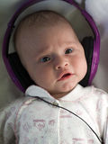 Baby with headphones. Baby with lilac headphones close-up Royalty Free Stock Photos
