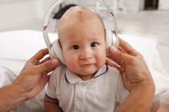 Baby with headphones listening to music Stock Photos