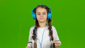 Baby in the headphones is listening to music. Green screen stock footage