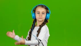 Baby in the headphones is listening to music. Green screen stock video