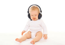 Baby in headphones sitting on white background Royalty Free Stock Photos