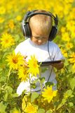 Baby in headphones and tablet. Funny baby in headphones and tablet in sunflower Royalty Free Stock Photo