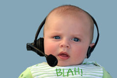 Baby with a headset. On a blue background Stock Images