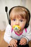 Baby with headset pacifier. Cute portrait of a baby girl wearing a headset or earphones with a pacifier in her mouth stock photos