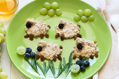 Baby healthy breakfast: oatmeal sheeps decorated berries Stock Photo