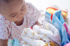 Baby with heap of colorful clothes in the room Stock Photos