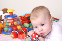 Baby and heap of toys. Portrait of 4months baby with colorful toys Stock Image