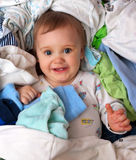 Baby in heap of wear Royalty Free Stock Photography