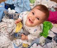 Baby in heap of wear Stock Photos