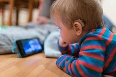 Baby with hearing aid. Partially deaf Baby with hearing aid is watching animated tale on smartphone Stock Image