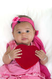 Baby with heart pillow on a bed. 6 months old baby with heart shaped pillow on a bed Stock Image